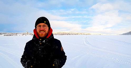 Mann mit Winterbekleidung steht im Schnee.